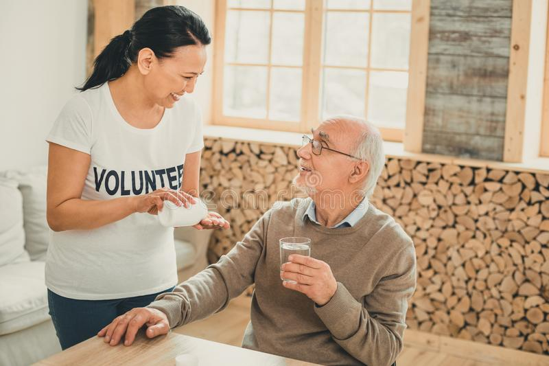Laughing lady wearing with t-shirt with text having workday. Thoughtful adult. Laughing lady wearing with t-shirt with text having workday in modern nursing home royalty free stock photo