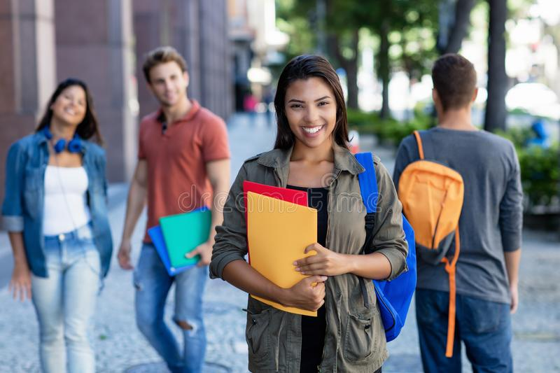 Laughing latin american young adult woman walking in city with group of students royalty free stock images