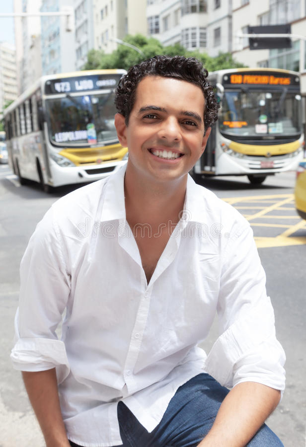 Laughing latin guy waiting for the bus in the city. With traffic in the background royalty free stock photography
