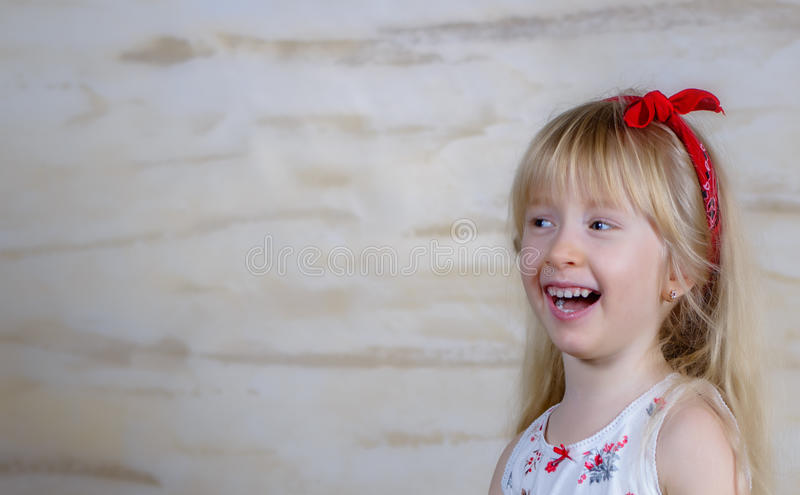 Laughing little blond girl with a red bow royalty free stock photo
