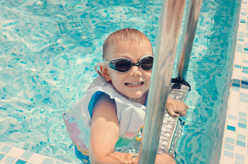 Laughing little boy climbing out of a pool stock image