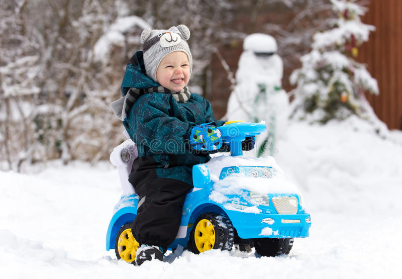 Laughing little boy drives toy car on snow. In winter stock image