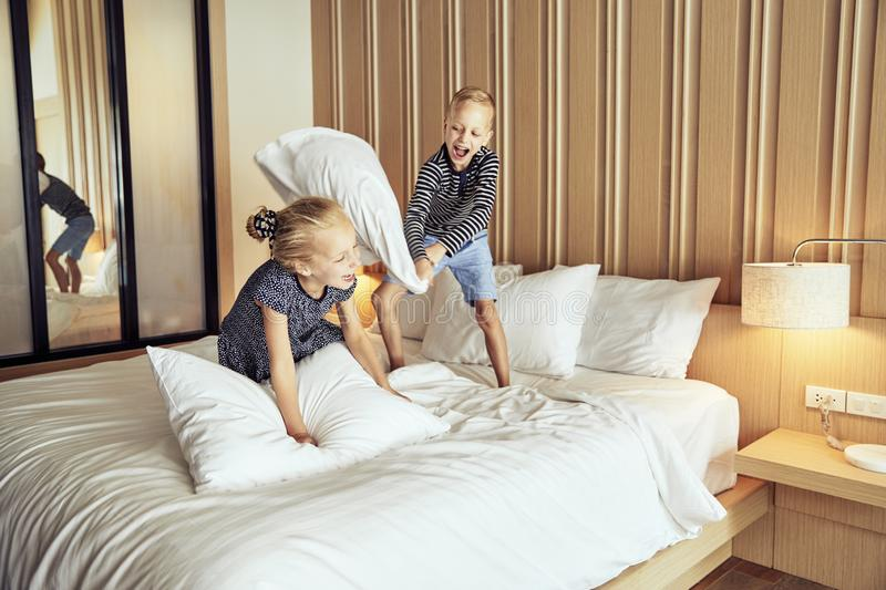 Laughing little boy having a pillow fight with his sister stock photos