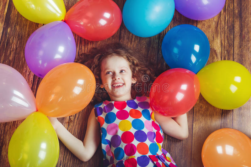 Laughing little girl in birthday party lying on wooden floor. Happy childhood concept royalty free stock photography