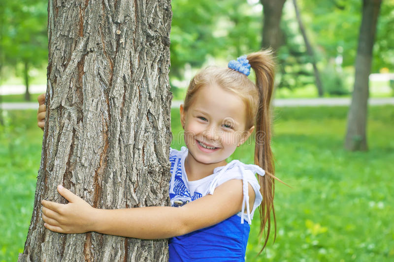 Laughing little girl hugging tree stock images