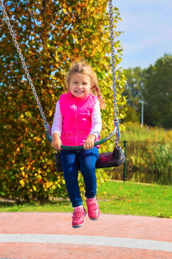 Laughing little girl swinging on a swing. stock photo