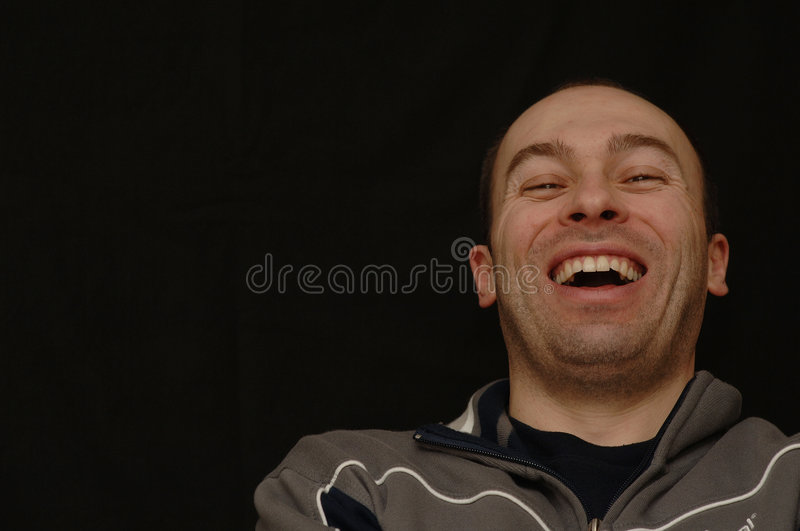 Laughing Man. Casually dressed, laughing man standing against a black background stock photography