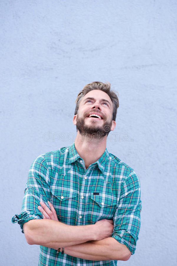 Laughing man with arms crossed looking up. Portrait of a laughing man with arms crossed looking up stock images