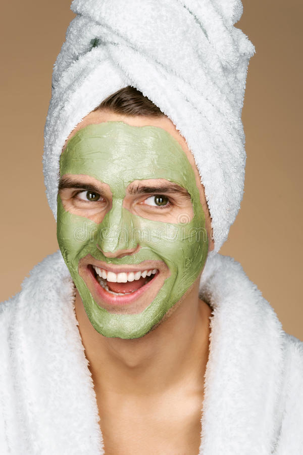 Laughing man with facial mask of avocado. stock photography