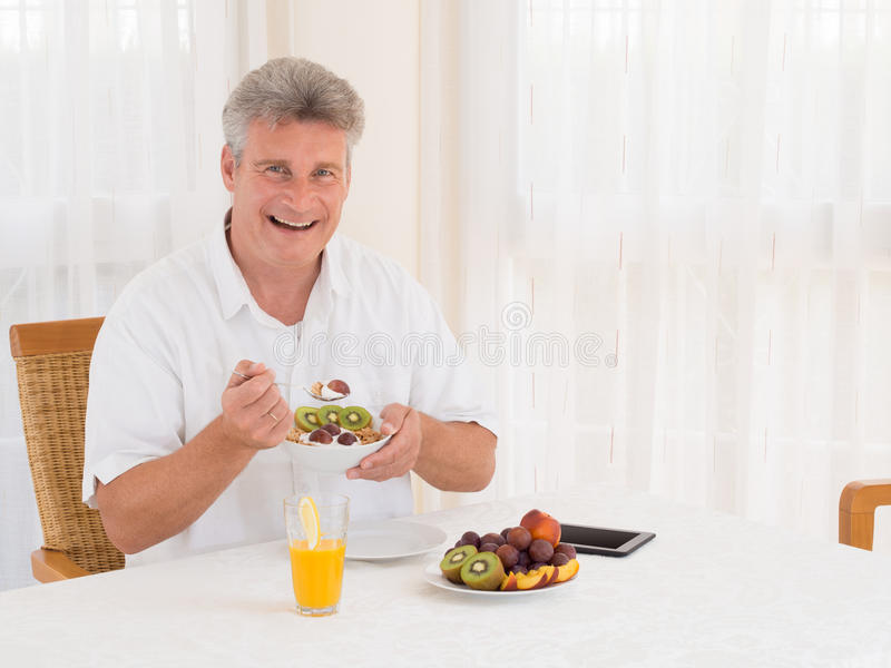 Laughing mature man eating a healthy cereal breakfast stock image