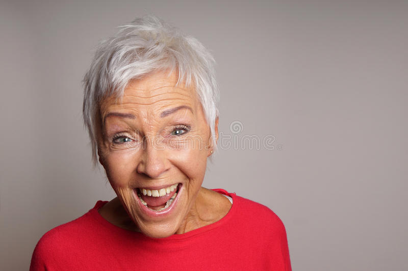 Laughing mature woman in her sixties stock image
