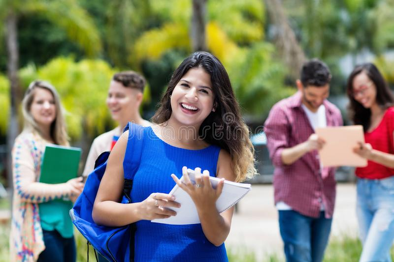 Laughing mexican female university student with group of students stock photo