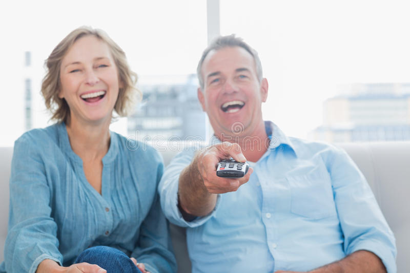 Download Laughing Middle Aged Couple Sitting On The Couch Watching Tv Stock Image - Image: 33052119