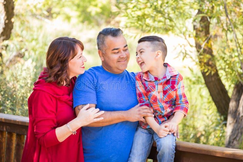 Laughing Mixed Race Caucasian and Hispanic Family At The Park. Mixed Race Caucasian and Hispanic Family At The Park stock photo