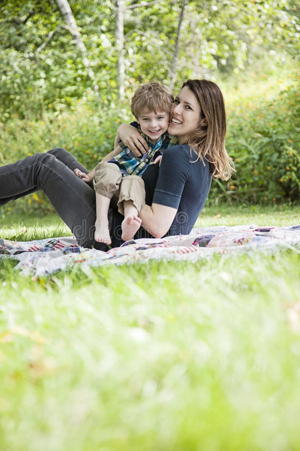 Laughing mother and child playing outside. Mother and son playing and laughing on blanket outdoors royalty free stock photography