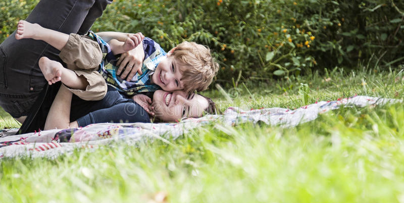 Laughing mother and child playing outside. Mother and son playing and laughing on blanket outdoors royalty free stock photo