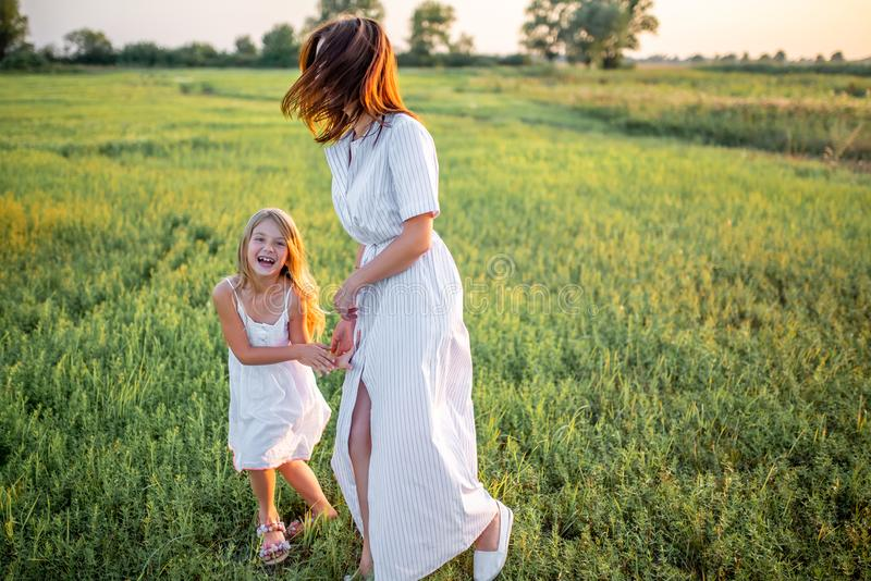 laughing mother and daughter in white dresses having fun royalty free stock image