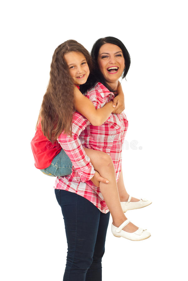 Laughing mother give piggyback to girl stock images