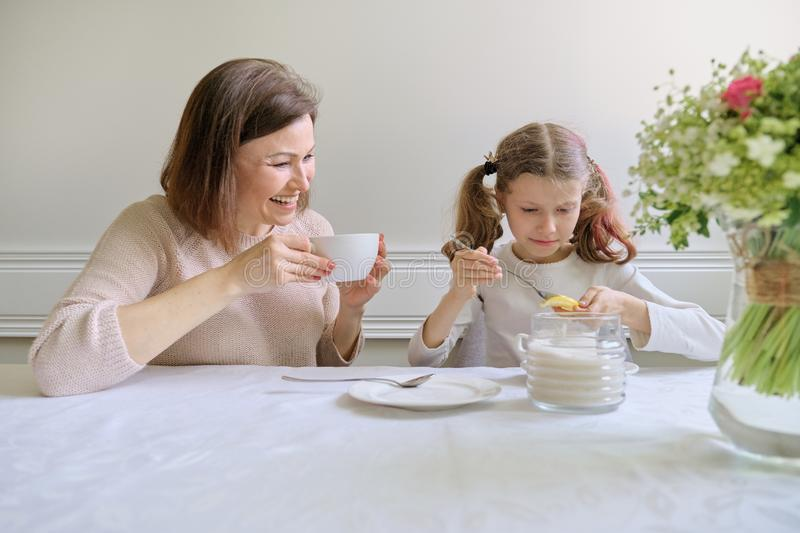 Laughing mother and daughter drinking from cups and eating lemon royalty free stock photography