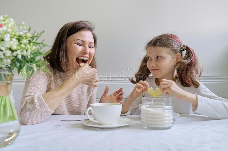 Laughing mother and daughter drinking from cups and eating lemon stock photography