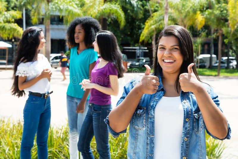 Laughing native latin american woman showing thumb with group of. Laughing native latin american women showing thumb with group of girlfriends outdoor in the stock photo