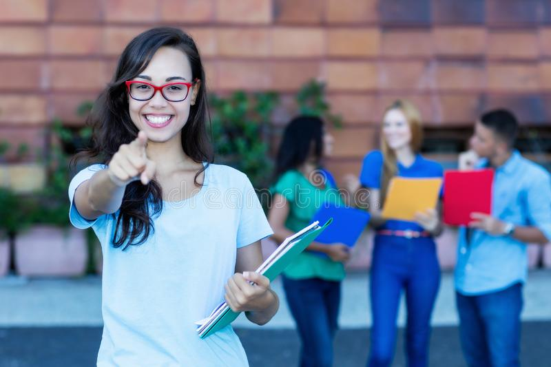 Laughing nerdy german female student with group of students stock photo