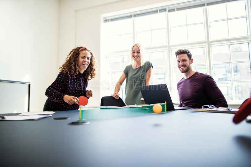 Laughing office colleagues playing table tennis during a work br stock image