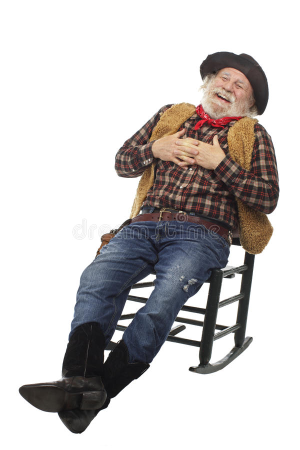 Laughing old cowboy leans back in rocking chair stock images