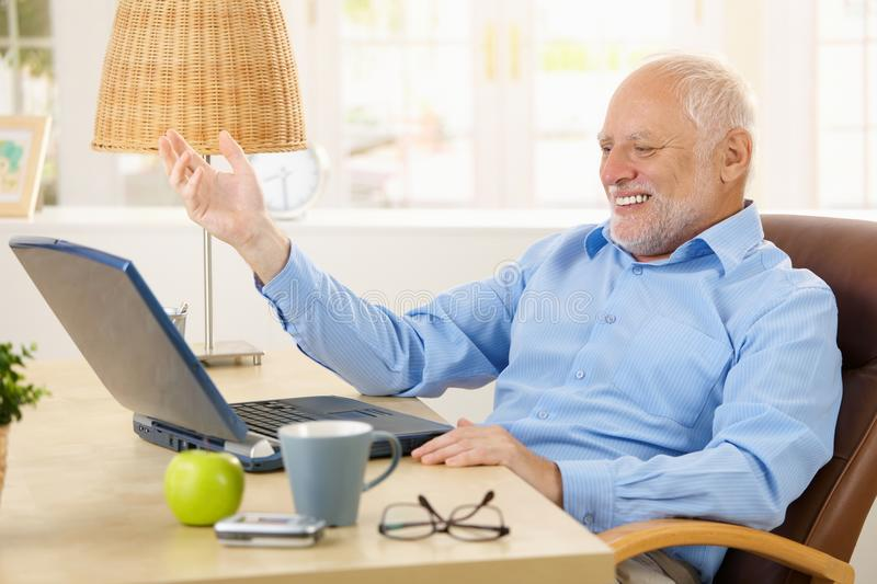 Laughing old man using laptop. Computer at home, looking at screen, gesturing