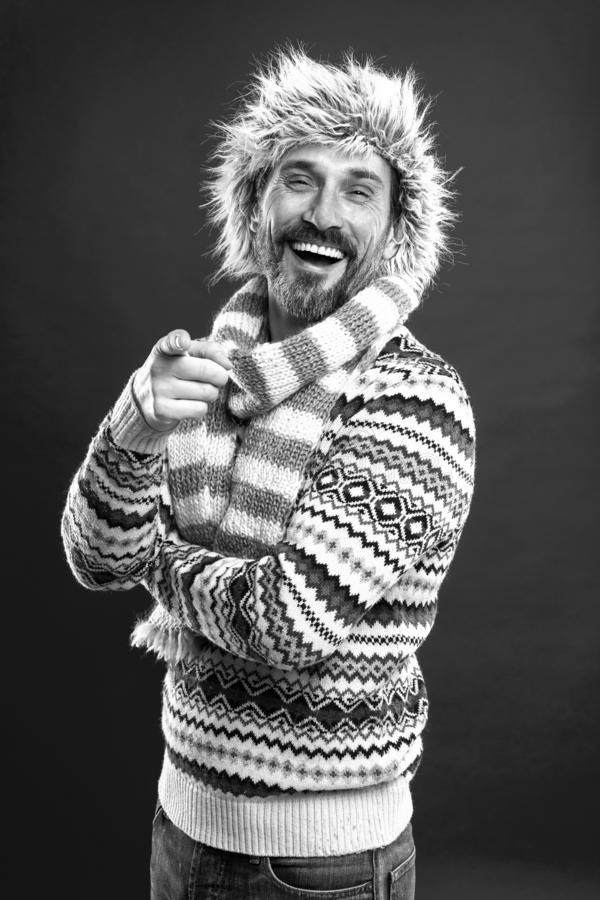 Laughing out loud. Bearded man accessorizing sweater with hat and scarf. A winter ensemble protects him from cold stock photography