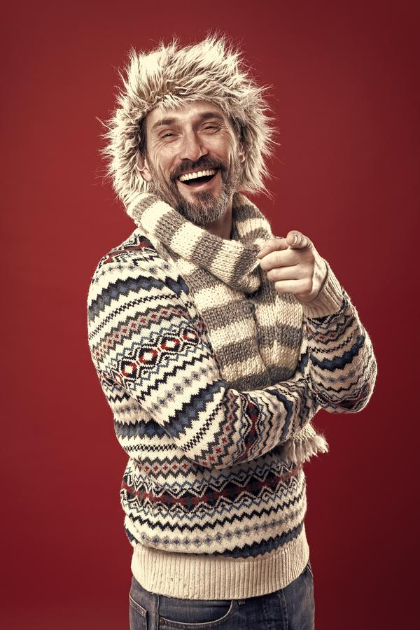 Laughing out loud. Bearded man accessorizing sweater with hat and scarf. A winter ensemble protects him from cold. Winter wardrobe for man. Mature fashion stock images