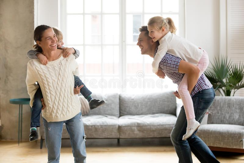 Laughing parents giving children piggyback ride playing together royalty free stock photography
