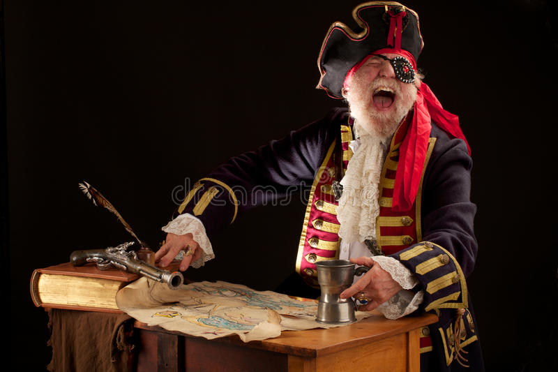 Laughing pirate with treasure map royalty free stock photography