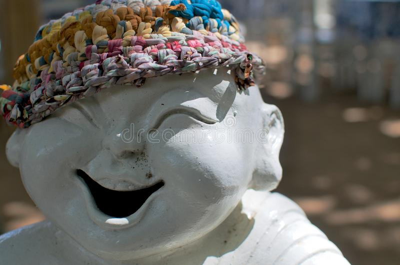 Laughing porcelain statue at the beach royalty free stock image