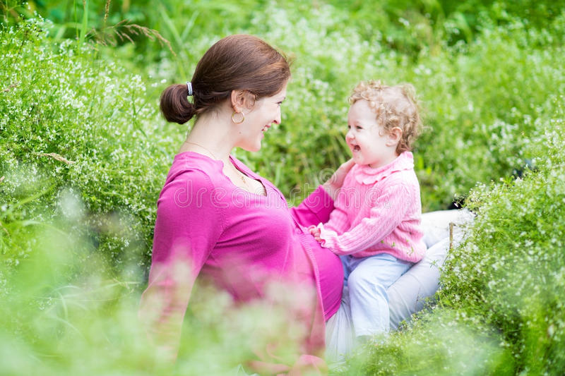 Laughing pregnant mother playing with her one year old baby stock images