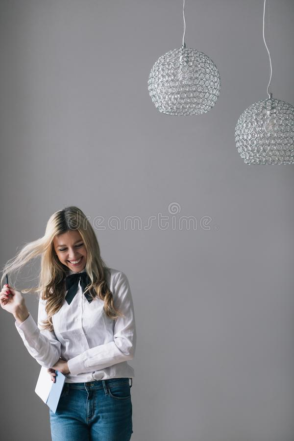 Laughing pretty blond woman in jeans and a white shirt standing by the wall with a notebook. stock photos