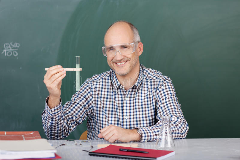 Laughing science teacher holding up a test tube stock images