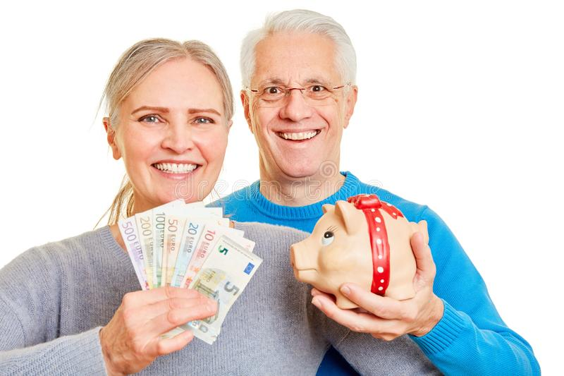 Senior couple with money and piggy bank stock images