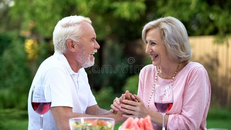 Laughing senior couple having fun during dinner, positive emotions, happiness royalty free stock photography