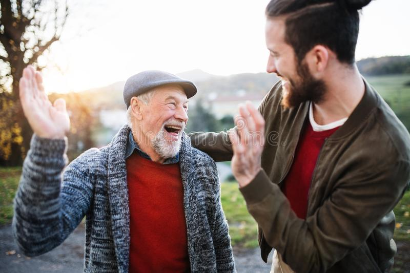 Laughing senior father and his son on walk in nature, giving high five. stock photography