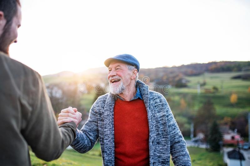 Laughing senior father and his son on walk in nature, shaking hands. Laughing senior father and his young son on a walk in nature, shaking hands stock photos