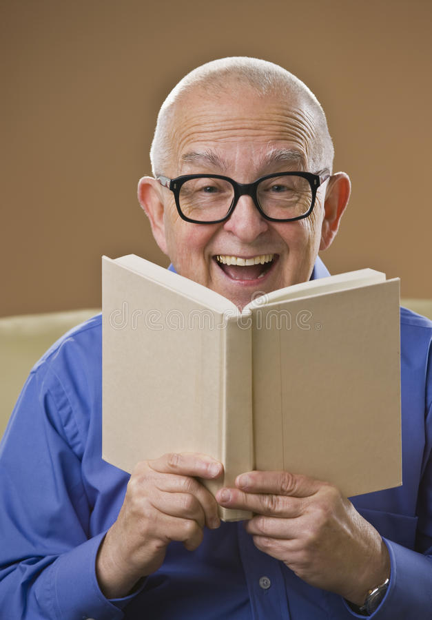 Laughing senior male reading a book royalty free stock photo