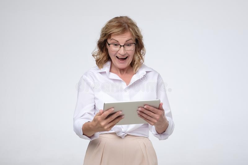 Laughing senior woman using tablet computer to buy some stuff stock images