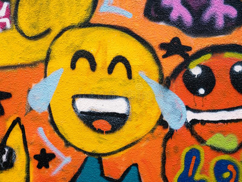 Laughing smiley face emoji graffiti. Street art colorful laughing smiley street art graffiti emoji face stock photography