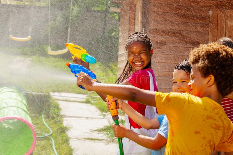Girl smile holding water gun in group kids game stock images
