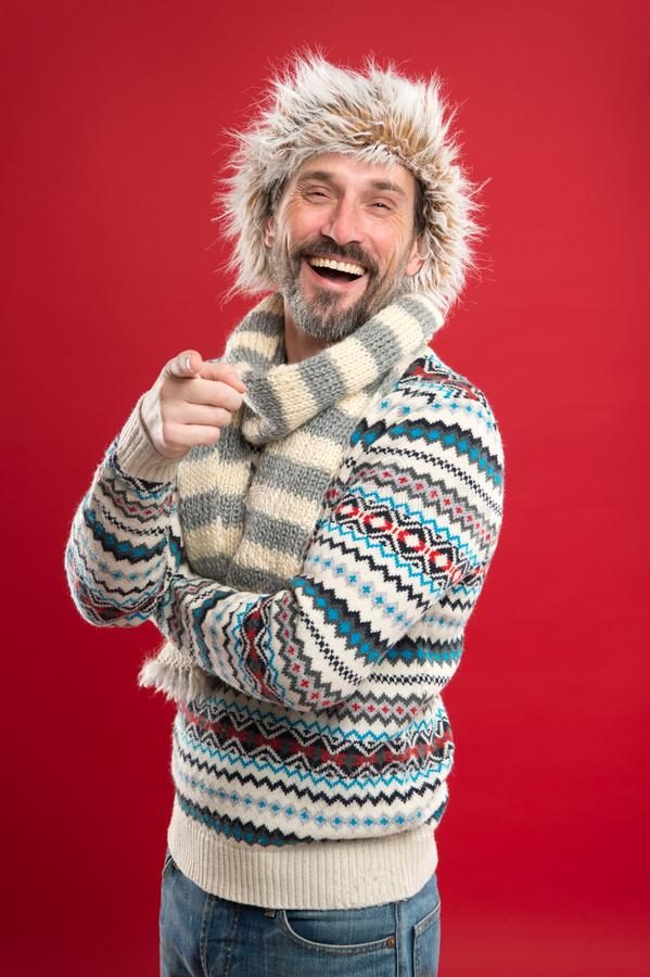 Laughing at something funny. Mature fashion model in cold weather style. Winter male wardrobe. Bearded man accessorizing. Sweater with hat and scarf. A winter stock photo
