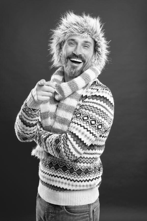 Laughing at something funny. Mature fashion model in cold weather style. Winter male wardrobe. Bearded man accessorizing. Sweater with hat and scarf. A winter royalty free stock photos
