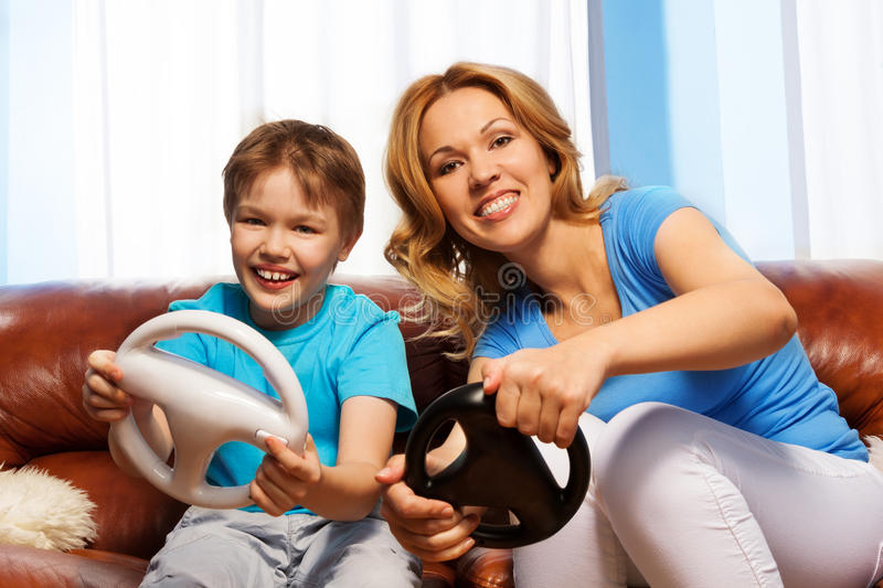 Laughing son and mom driving steering wheels stock image