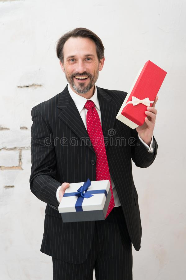 Laughing stylish mature man holding two presents while suggesting one present to you stock photos
