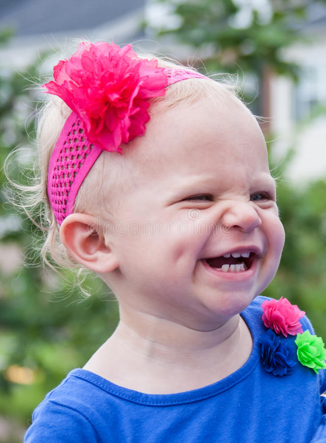 Laughing Toddler Girl. Closeup of blonde toddler girl with dimple and wrinkled up nose, laughing stock photos